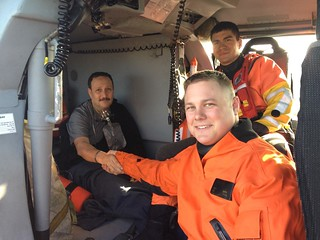 Coast Guard Petty Officer 3rd Class Mitchell Ulrich, an avionics electrical technician at Air Station Houston, shakes the hand of a rescued medevac patient, March 1, 2014, at the Scholes International Airport in Galveston. It was Ulrich's first search and rescue case after getting qualified as a duty flight mechanic.