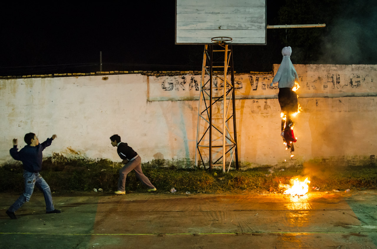 Niños arrojan piedras al Judas kái mientras es incinerado pasado las 00:00 del día 26 de junio en el sanjuanazo que se realizó en la ciudad de San Juan este año. (Elton Núñez)