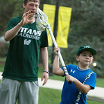 hmc018 -- A lacrosse team member coaches 7-year-old Lucas Chiszar during Family Fun on the Quad.