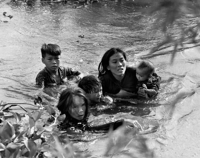 Vietnamese civilians cross a river to escape attack on village