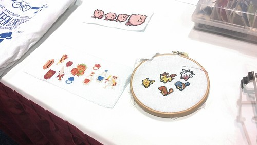 Embroidery hoop with small embroidered 8-bit style Pokemon designs. Next to it on the table are Legend of Zelda and Kirby designs.