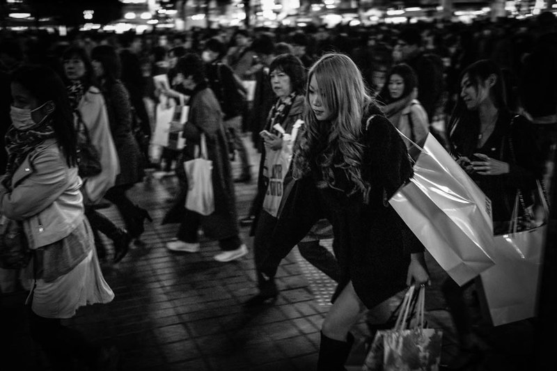 A pretty girl laden with shopping bags crossing the world's busiest junction at the Shibuya scramble crossing.