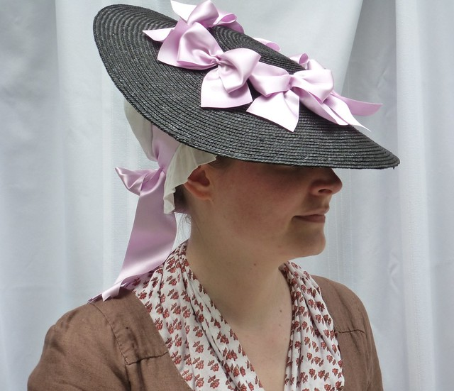 black straw hat trimmed with lavender ribbon bows