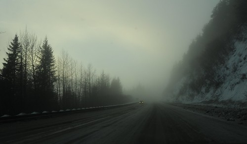 Clouds in the pass, wide, sanded Sterling Highway, snow and trees, with a single truck lights on, traveling in the winter, Kenai Peninsula, Alaska, USA by Wonderlane