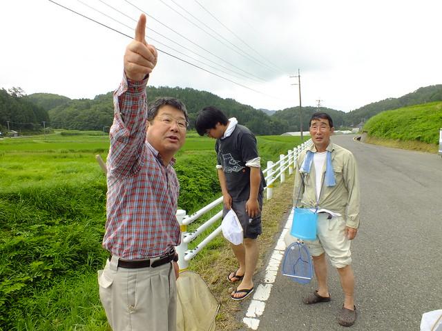 山の向こうを指差す内藤先生.似たような環境の川が流れているが,あちらにはカワシンジュガイは生息していないことを聴いた.