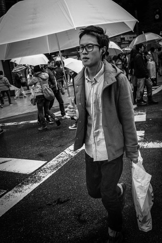 A young man in Shinjuku crossing the road in the rain.