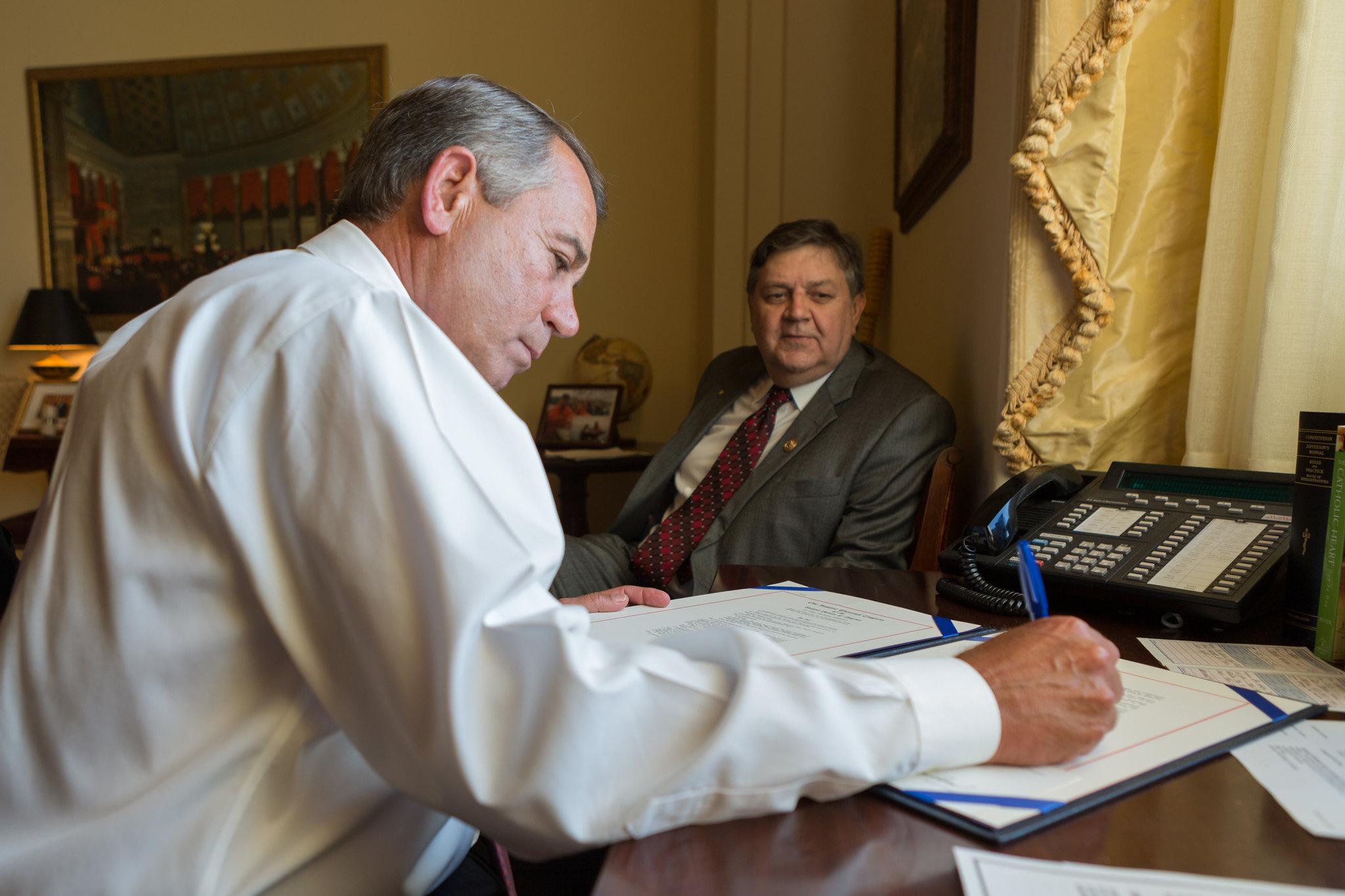 Speaker John Boehner signs the Sleeping Bear Dunes National Lakeshore Conservation and Recreation Act as Rep. Dan Benishek (R-MI), the sponsor of the House version of the legislation, looks on.