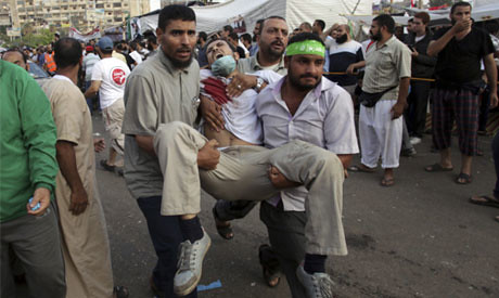 A wounded man being carried to a field hospital in Nasr City, Egypt on July 27, 2013. Over 100 people were killed in one day by the military. by Pan-African News Wire File Photos