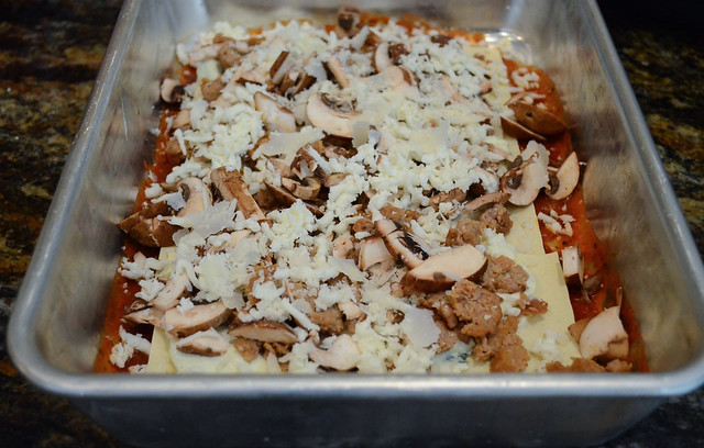 Shredded cheese is added on top of the sausage and mushrooms.