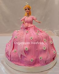 torte(0.0), cake(1.0), baked goods(1.0), sugar paste(1.0), food(1.0), cake decorating(1.0), birthday cake(1.0), dessert(1.0), pink(1.0), doll(1.0), barbie(1.0), toy(1.0),