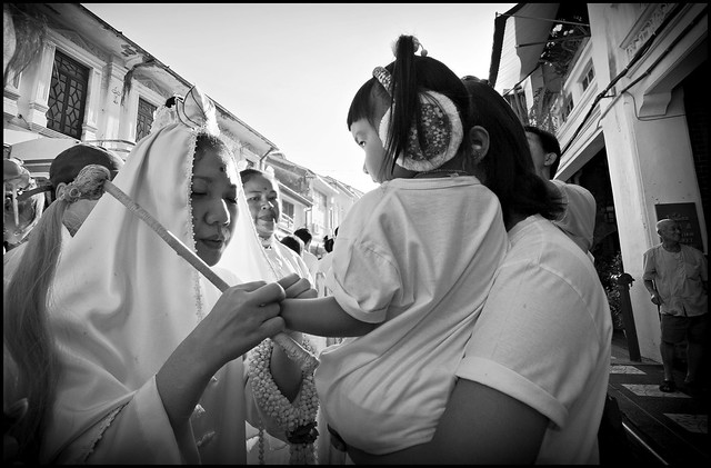 Small girl receiving a blessing from a female Ma Song at the Phuket Vegetarian Festival 2013