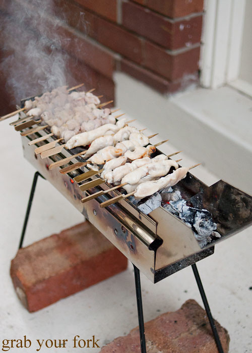 yakitori chicken skewers on an arrosticini charcoal grill at a stomachs eleven japanese dinner