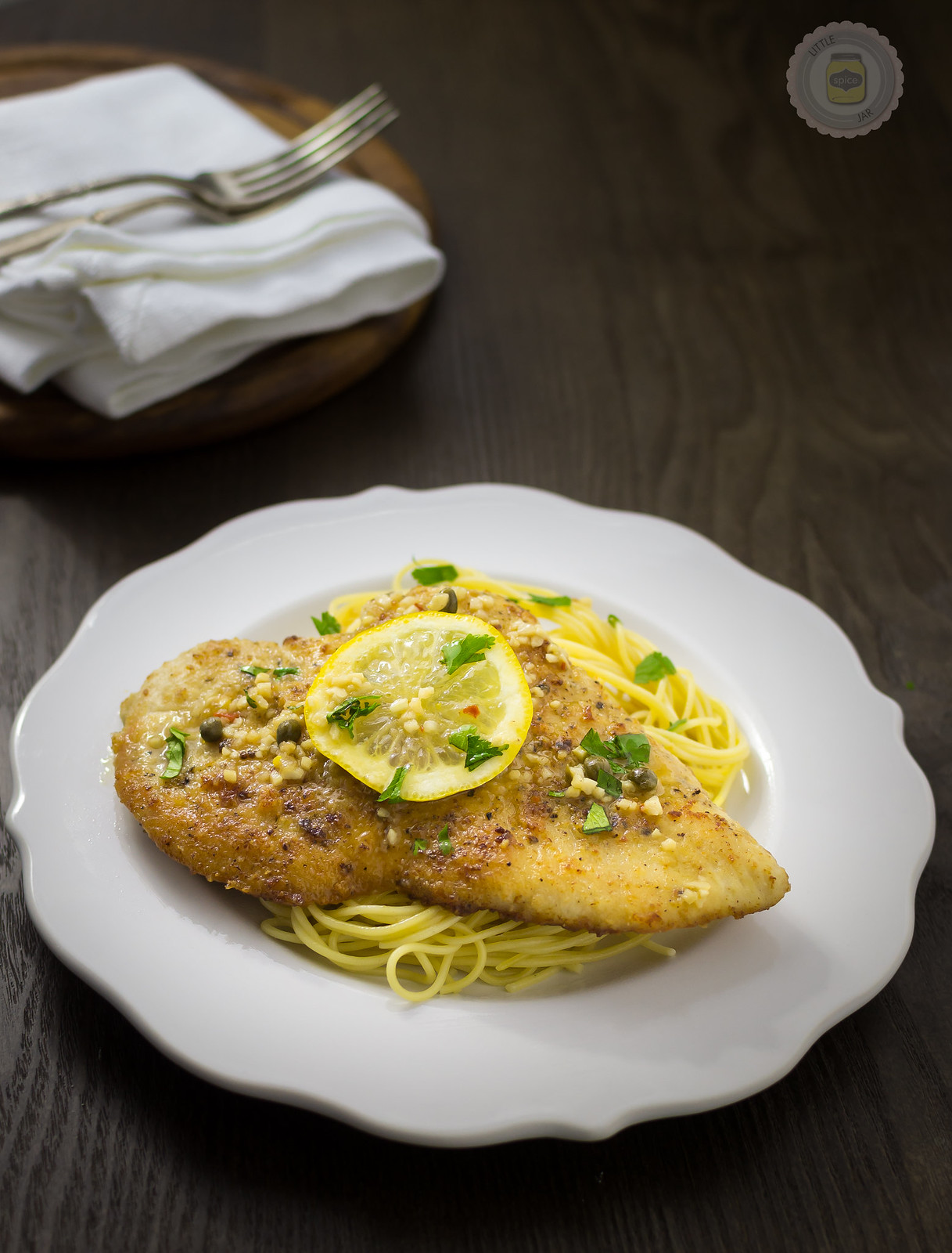 plate with prepared spaghetti topped with chicken breast with lemon slice and parsley