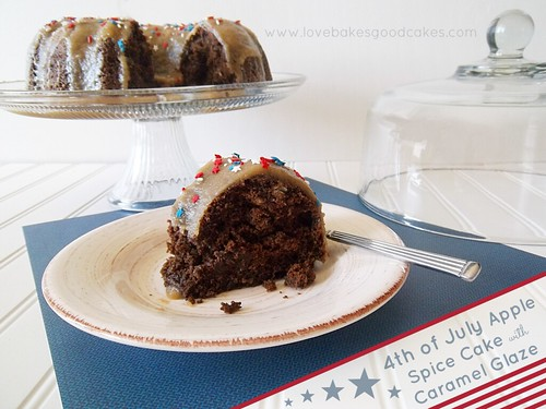 4th of July Apple Spice Cake with Caramel Glaze piece on plate with fork. Cake on cake stand in background.