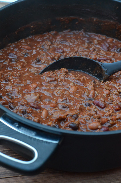 A black spoon stirs the chili in a pot.