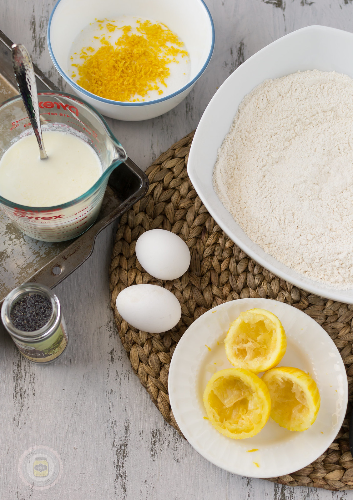 measured ingredients for lemon muffins on white surface