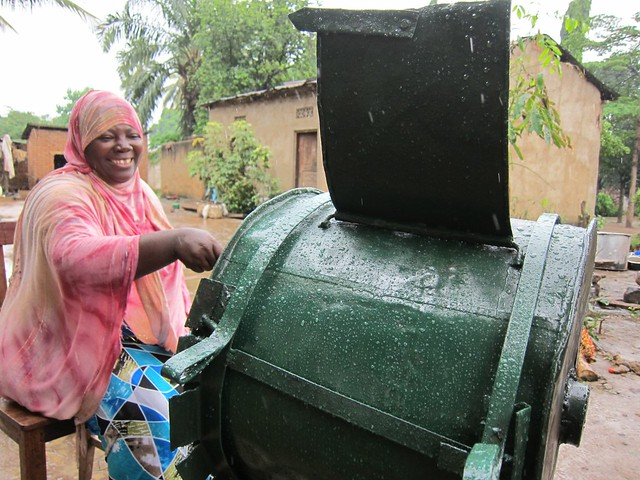 A woman uses a palm oil extractor machine.