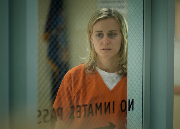 Piper, a blonde white woman, behind a prison door