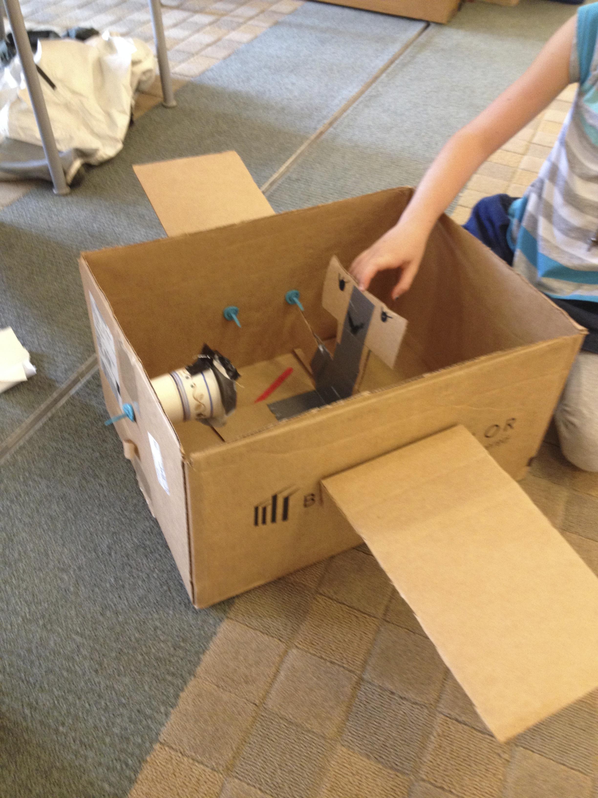 Cardboard robot rides in a cardboard car.