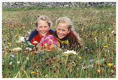 SCANNED-IN PRINT:  Christine and Angela playing between the wildflowers in Galway 1997