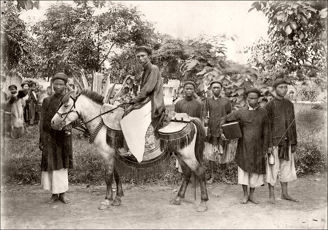 Indochina - Tonkin - Mandarin on horseback accompanied by his porters