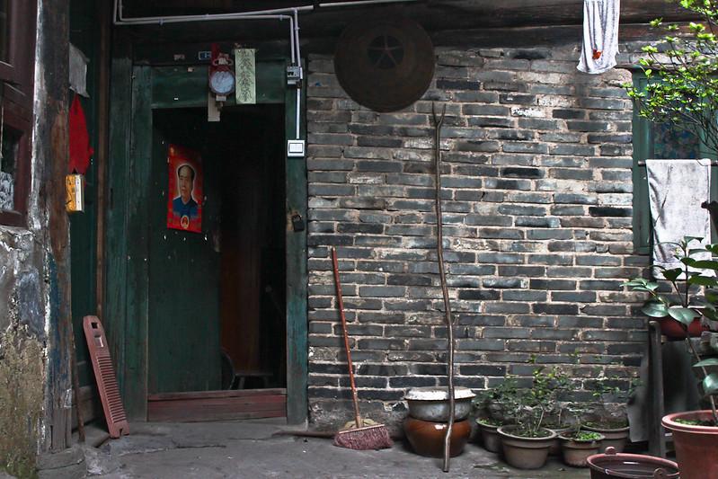 Puerta de una casa de la aldea de Hongjiang con el retrato del omnipresente Mao Zedong.