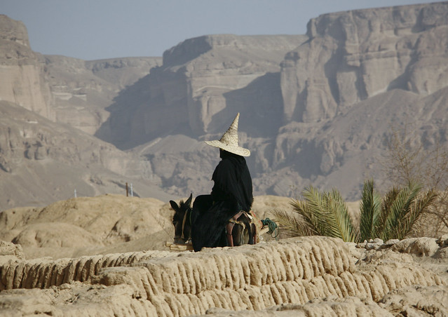 Woman Wearing A Tall Cone Hat And Riding On A Donkey In Rocky Land, Hadramaut, Yemen
