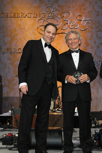 Two men in tuxedos, one is holding an award.