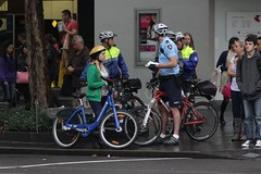Victoria Police bicycle squad talk to a fellow cyclist on Swanston Street