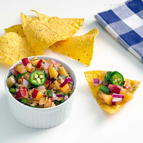 Plum Salsa in white ramekin with tortilla chips and napkin in background