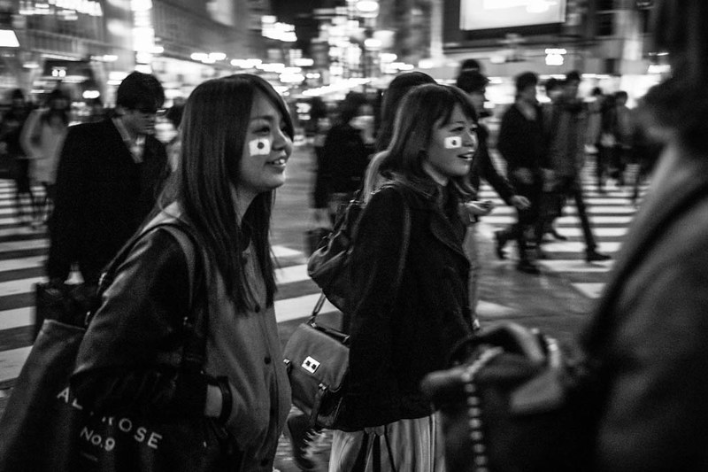 2 girls with the Japanese flag emblazoned on their faces crossing the road at Shibuya, Tokyo