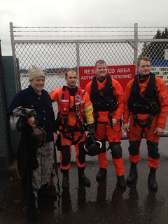 John Delong, of Sitka, Alaska, stands with Petty Officer 2nd Class Brendan Dent, Petty Officer 2nd Class Jason Vaughn and Petty Officer 3rd Class Ryan Ransom from Coast Guard Air Station Sitka after his rescue from the Carmel Mountain area near Sitka Nov. 19, 2014. Delong was stranded on the island while hunting after his boat became submerged. (U.S. Coast Guard photo by Cmdr. Pete Melnick)