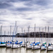 parked yachts in harbour with cloudy skies
