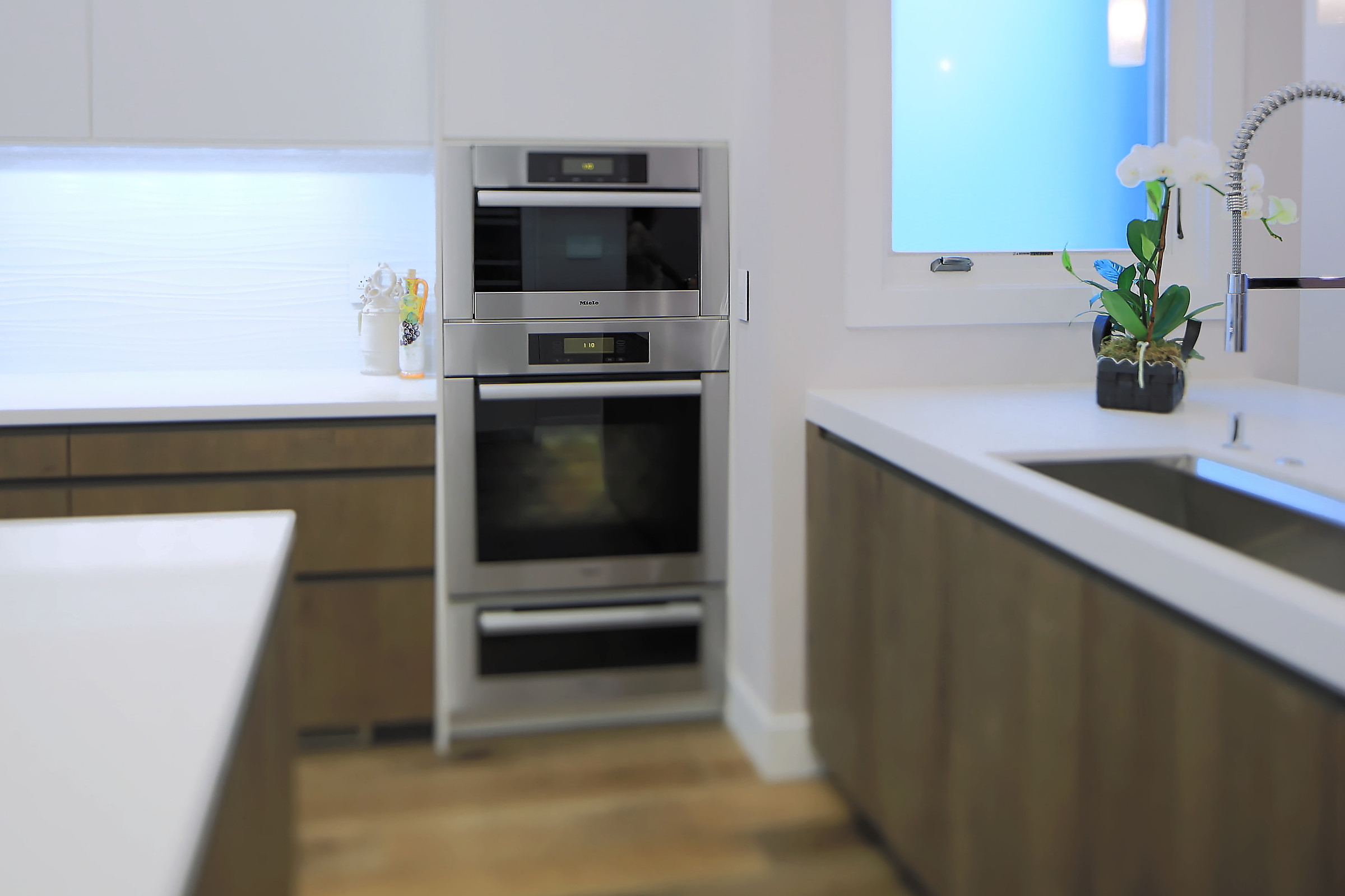 Tucked behind a wall with easy access are modern Miele appliances.