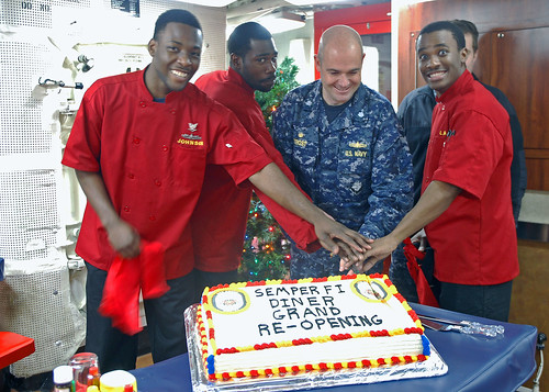 EVERETT, Wash. - (left to right) Culinary Specialist 3rd Class McHale Johnson, Culinary Specialist 3rd Class Jeron K. Petersen, Cmdr. Bryant P. Trost, commanding officer of USS Shoup (DDG 86), and Culinary Specialist Seaman Esaie Lira celebrate the reopening of Shoup's galley with a cake cutting.