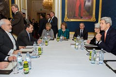 U.S. Secretary of State John Kerry, Baroness Catherine Ashton of the European Union, and Foreign Minister Javad Zarif of Iran, joined by their respective advisers, sit at a table in Vienna, Austria, on November 21, 2014, before beginning the second of their most recent three-way discussions about the future of Iran's nuclear program. [State Department photo/ Public Domain]