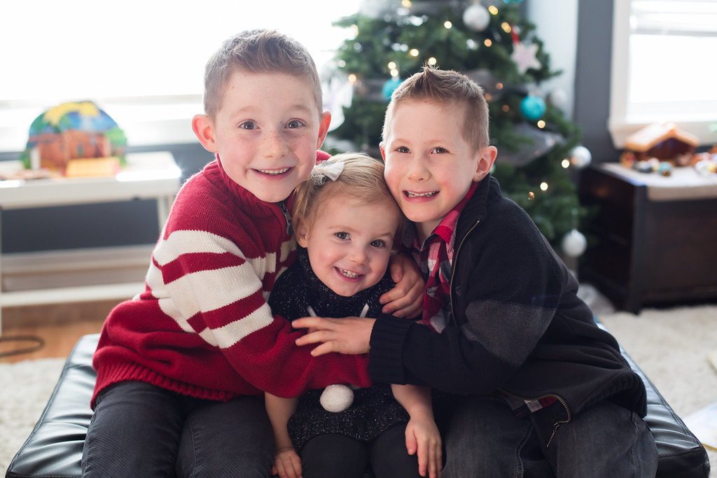 Children sitting in front of the Christmas tree