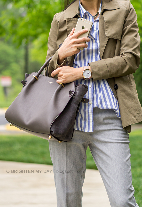 olive green swing trench, blue striped button up shirt, gray trousers, oversized watch