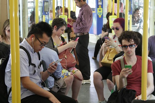 Tram full of passengers absorbed in their smartphones