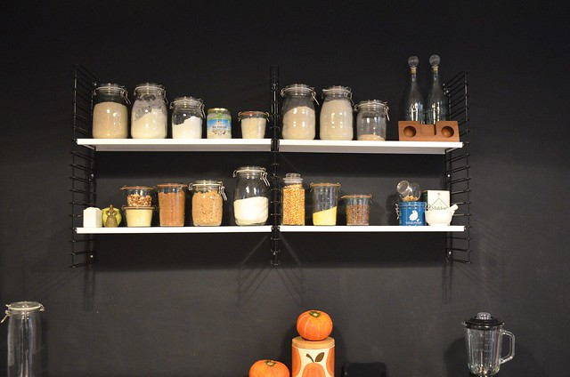 Berlin apartment_ kitchen string shelves on black wall with food storage jars