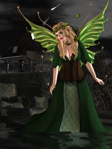 Image Description: Woman in a long, green gown standing in font of a piano with pages flying off of it.
