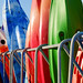 Small photo of Bright coloured canoes in a row