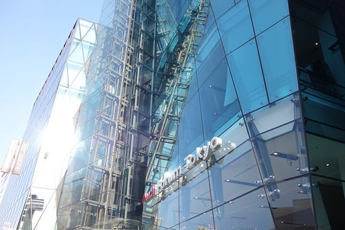 "Shibuya_27 渋谷の明治通りに面した所にある高層ビルディングを撮影した写真。 右の ""THE ICEBERG ビルディング"" の前面はターコイズブルー色のガラス張りで複雑な三次元ジオメトリック構造をしている。 エレベーターのワイヤーやフレーム構造がガラス面に映り込んでいる。 左の ""THE ICEBERG ビルディング"" は前面が数多の三角形のガラス張りである。"