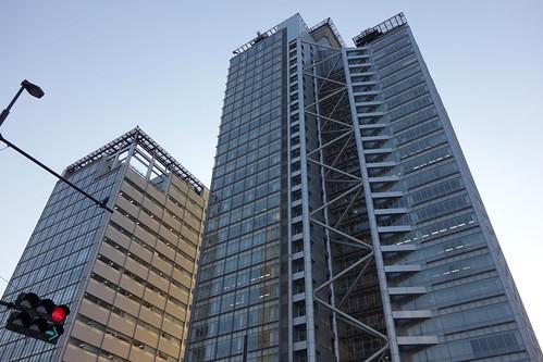 """Shinjuku_3 新宿で高層ビルディング群を撮影した写真。 逆光の夕陽に照らされている。 左は """"中野坂上セントラルビル"""" で右は """"中野坂上サンブライトツイン"""" である。 右のビルディングは前面中央を縦に上から下まで鉄骨トラス構造が連なっている。"""