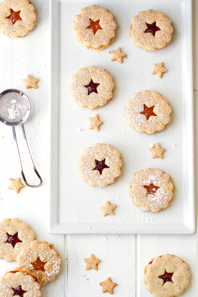 Raspberry Almond Linzer Cookies - Almond shortbread cookies sandwiched together with raspberry jam in the center. These cookies are sooo good! | Littlespicejar.com