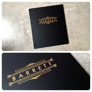 Custom graphic design portfolio book with engraved color fill treatment in gold on matte black acrylic