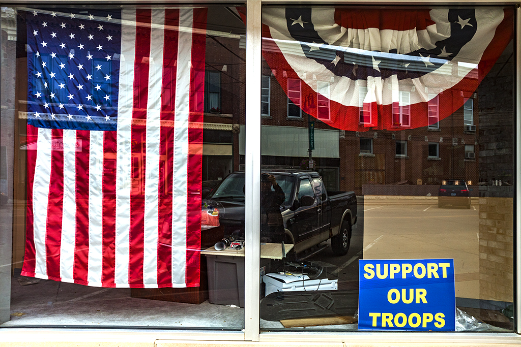 Flag-and-SUPPORT-OUR-TROOPS-sign-in-window--Grinnell