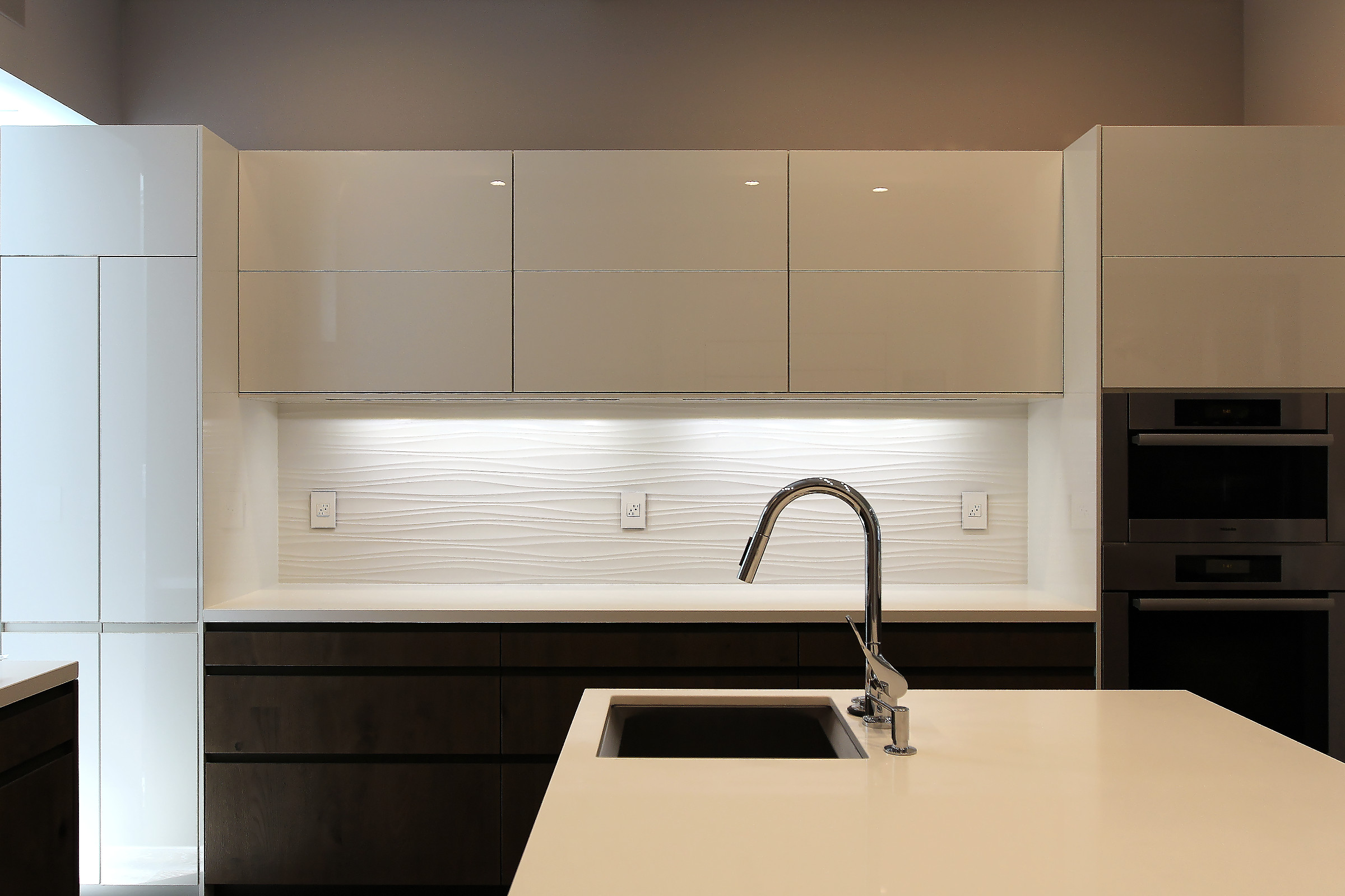These gloss white Leicht wall cabinets have electric motors (Blumotion) that open and close them with a touch.