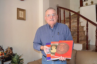 Howard A. Daniel III with his catalogs of Cambodia, Lao and Vietnam numismatics