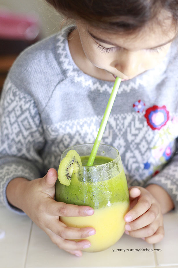 A little girls drinks a tropical kiwi smoothie.